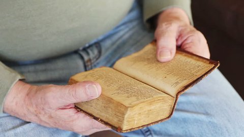 Senior man reading a vintage book of Psalms