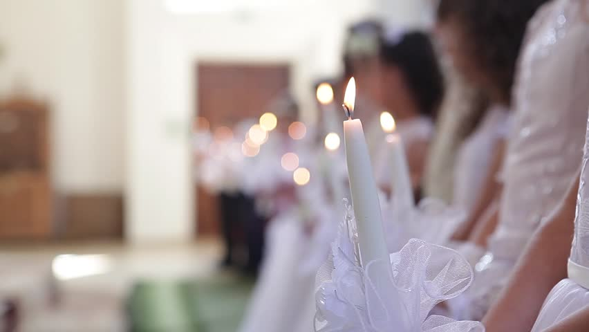 Children take the first communion in the church in white dresses holding candles in their hands.