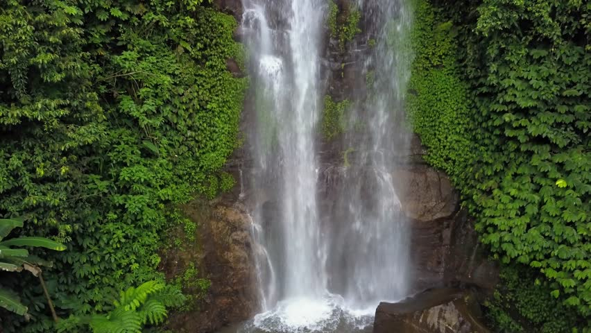 Aerial  ascending video drone shot of the Golden Valley waterfall in the Munduk jungle, Bali, Indonesia #1011337679