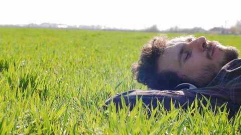 young male relaxing on the green grass and listen to music with big white headphones, laying in the summer fields
