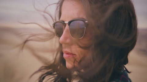 Close up portrait of Young Woman reflecting with hair blowing in wind looking at sunset at a desert oasis wearing green plaid long sleeve in Peru Slow Motion