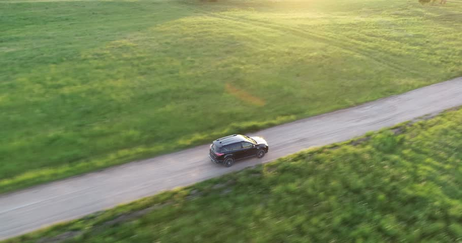 Aerial view of crossover SUV car driving along the empty gravel road through green meadows landscape on sunny morning. Drone chasing a car. | Shutterstock HD Video #1011354869