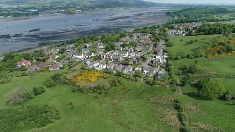 Aerial footage over woodland and yellow gorse covered hillside to the village of Langbank on the south shore of the Firth of Clyde.