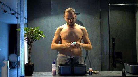 Young man in towel applying antiperspirant on his armpit in bathroom