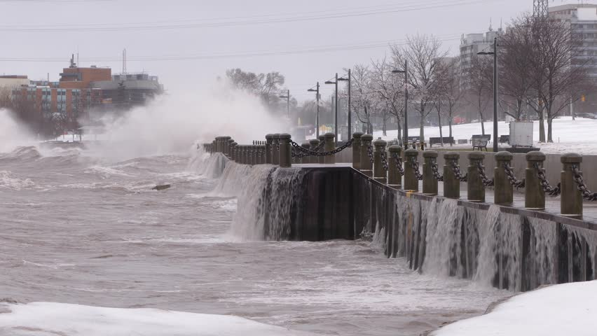 Huge powerful waves breaking at seawall in major severe storm in hurricane force winds
