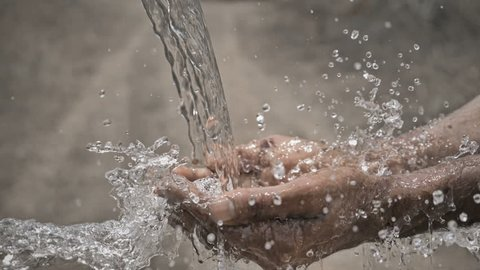 slow motion shot of pure and freshwater water falling on the farmer's hands against barren and dry farmland. Clean drinking water splashing on hands of the poor farmer in a drought affected area