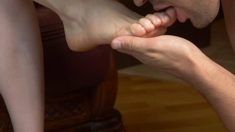 beautiful male with sexy lips sensually and romantically kissing and caressing the toes of an anonymous female. . 4k slow motion, close-up