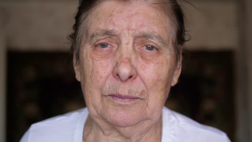 Close-up portrait of an elderly old Caucasian woman with a wrinkled face and pigmented spots. Suffers from tremors and Parkinson tremors and muscle twitching cheekbones and eyelids. 4K, 3840x2160 | Shutterstock HD Video #1011417479