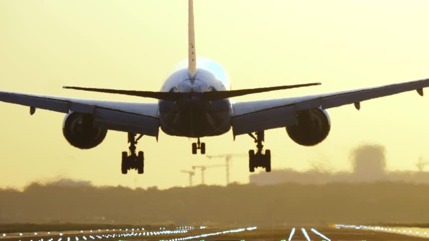4K Passenger airplane landing during sunrise.