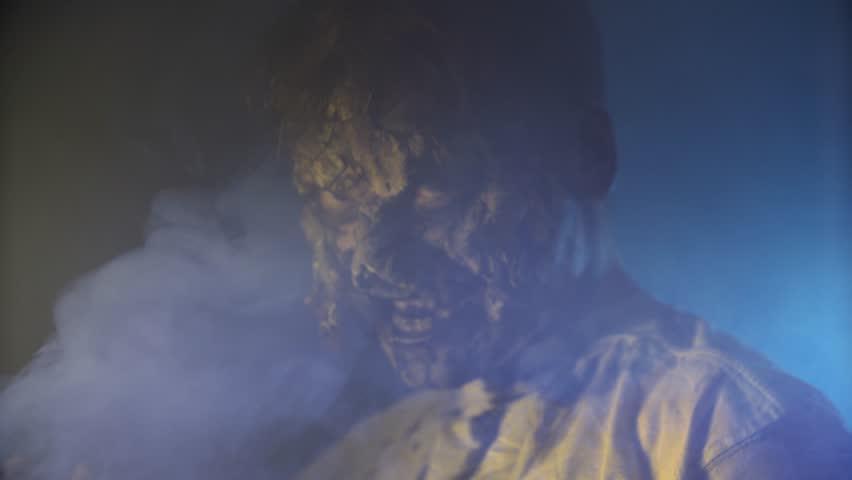 Scary zombie closeup on dark background in Halloween makeup | Shutterstock HD Video #1011440099