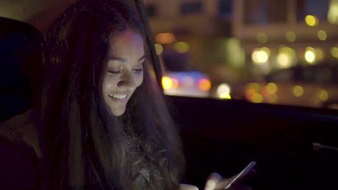 Happy Young Woman Texts On Her Smart Phone In Back Seat Of Car Stopped At A Red Light (Slow Motion)