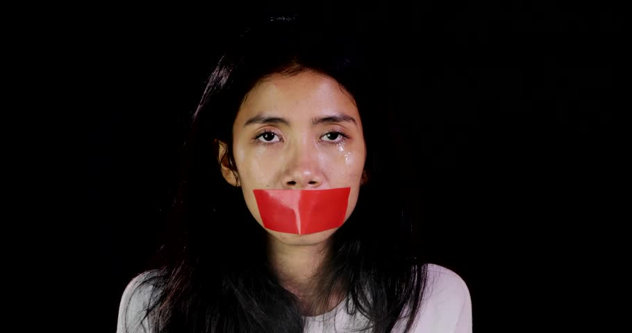 Concept of domestic violence or kidnapping. Sad woman with closed mouth using adhesive tape over dark background. Shot in 4k resolution