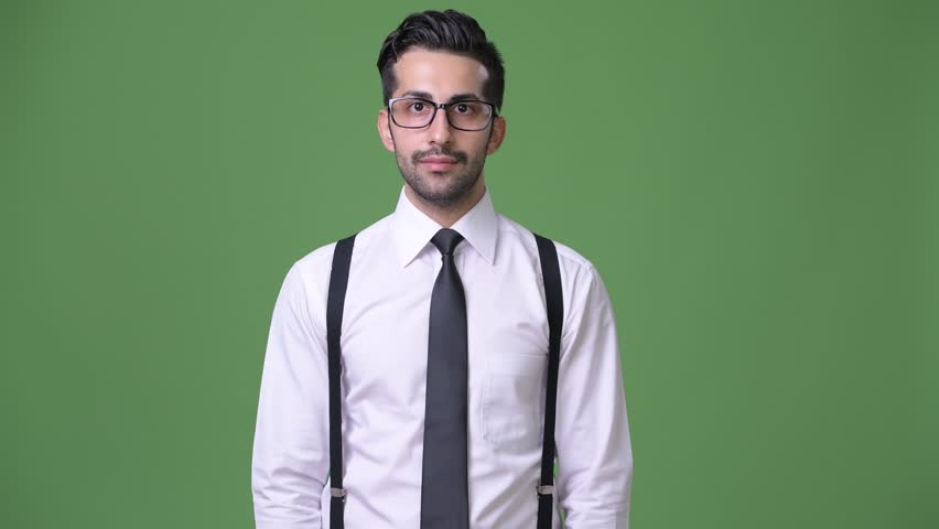 Young handsome bearded Persian businessman against green background | Shutterstock HD Video #1011456899