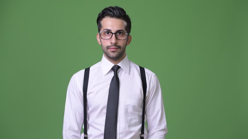 Young handsome bearded Persian businessman against green background | Shutterstock HD Video #1011456989