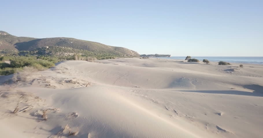 Forward aerial drone video slowly skimming over sand dune contours of Turkey's longest beach next to ocean and shrubs in Patara, Turkey. 4k at 23.97fps