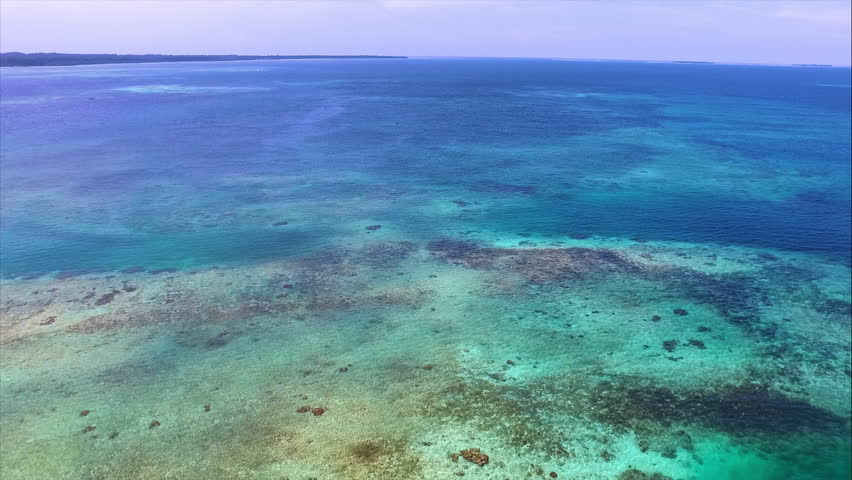 Boat sailing on pristine crystal Caribbean waters aerial drone. Aerial shot of a ferryboat with a clear turquoise seabed below. Caribbean Sea next to Cay Coral in Bocas del Toro islands in Panama.