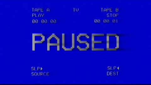 Analog capture (intentional heavy distortion fx): an old damaged VHS tape tracking a bad signal coming from a double deck, with the text Paused.