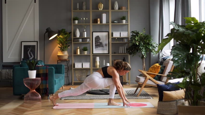 Attractive Caucasian woman in her thirties does yoga poses warrior king pigeon in the morning in stylish sunny spacious living room in elegant Scandinavian style decorated with sophisticated decor