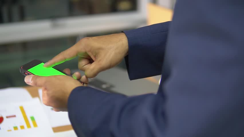 A businessman working on his mobile device in his office. The mobile device is in green screen mode.   Shutterstock HD Video #1011485789