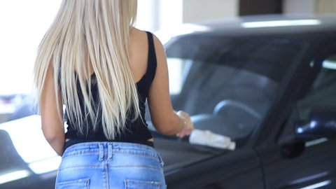 beautiful blonde girl with big booty and Breasts, with long legs in short denim shorts rubs the car after washing in the garage