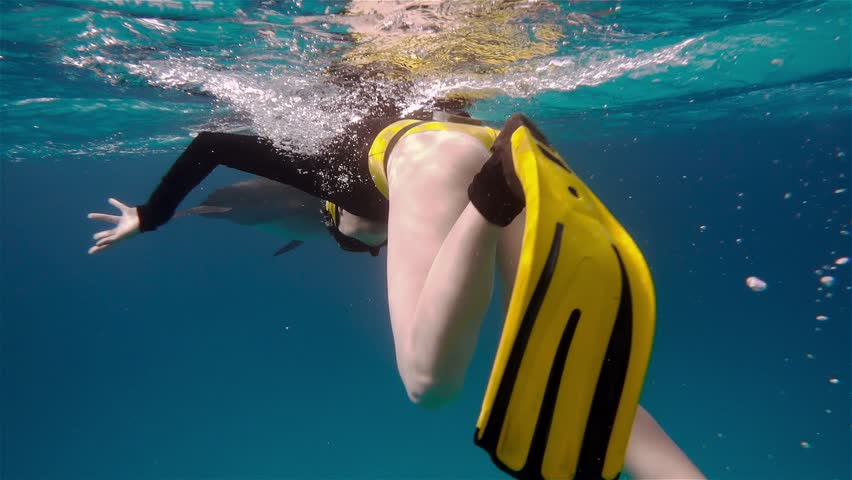 A freediver girl and dolphins in sea