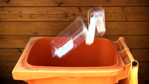 Slow motion shot of various household plastic items dropping into a recycle wheelie bin.