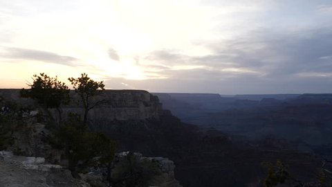 Zooming in on a sunset over the Grand Canyon USA to a steep rocky cliff on the southern rim
