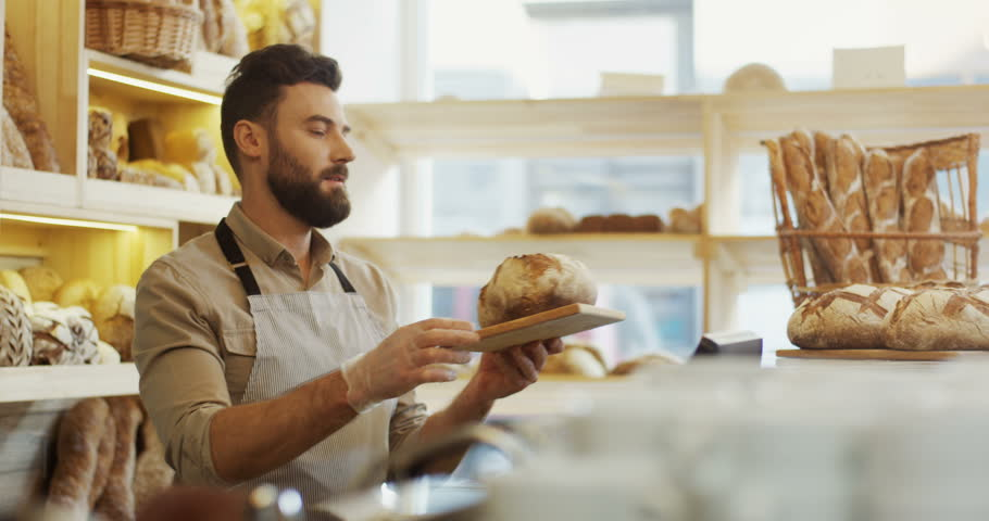 Young handsome man vendor in the apron bringing fresh bread to the counter in the bakery shop. Indoors | Shutterstock HD Video #1011537839