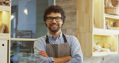 Portrait shot of the handsome man baker in glasses and apron turning to the camera and posing in the bakery shop. Close up. Indoor