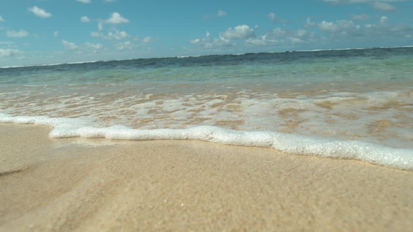 SLOW MOTION, CLOSE UP: Turquoise ocean waves roll in on the peaceful shore on tropical island. Bubbling wave coming from the sea sweeps the tranquil beach. Relaxing view of swell reaching sandy beach.