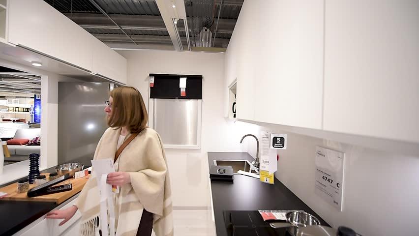 PARIS, FRANCE - CIRCA 2018: Modern IKEA furniture store woman customer browsing through diverse furniture, decoration warehouse goods - side view deciding to buy kitchen furniture new