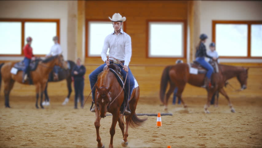 Young western rider focused on riding a pattern in slow motion 4K. Long shot of a male person on a horse in focus wearing a shirt and cowboy hat riding towards the camera. More riders in background. | Shutterstock HD Video #1011584939