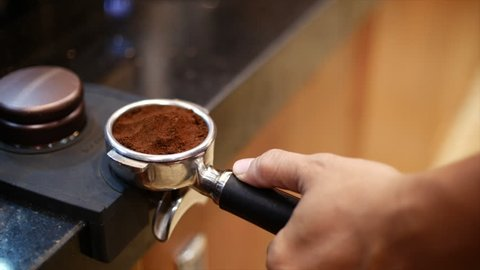 Making Ground Coffee with Tamping fresh coffee. Close-Up. Making coffee from start to finish.Tamping Fresh Ground Coffee. Professional barista.