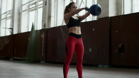 PAN of strong sportswoman in fitness top and leggings swinging kettlebell in empty gymnasium