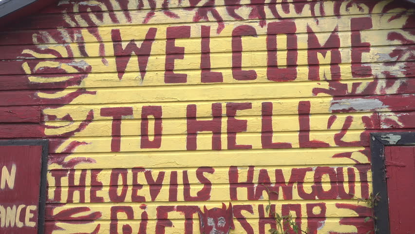 HELL, GRAND CAYMAN/CAYMAN ISLANDS - JANUARY 20, 2018: Welcome to Hell sign on gift shop, Caribbean, tilt down. Hell refers to an open space filled with clusters of short black limestone. | Shutterstock HD Video #1011611189