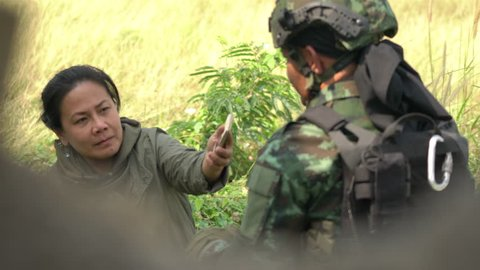 Soldier fieldwork interview with presswoman. Reporter unsafe area. Soldier holding gun weapon and waring armor uniform.