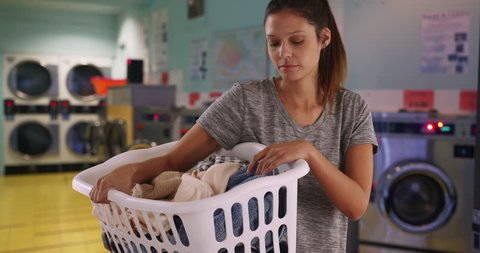 Serious young woman standing in laundry room with machines holding basket of clothes. College student on laundry day carrying basket of clothes to wash. 4k