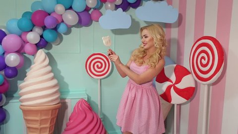 Emotional slender girl holds a large candy in the form of watermelon on a colorful bright background. Barbie the girl. Lollipops. Shop of sweets.
