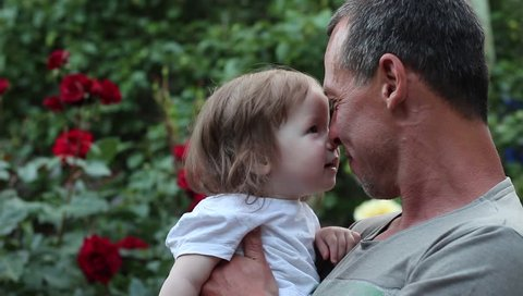 Father's Day. Smiling father and one year old girl. Happy dad with daughter on background of flowers. Adult male with gray hair
