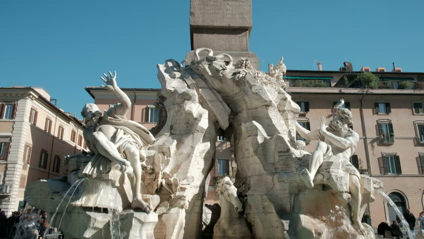 Slow low angle camera tilt down from top of Egyptian obelisk to marble Bernini sculptures of center Fiumi Fountain in Piazza Navona. 4K UHD at 29.97fps