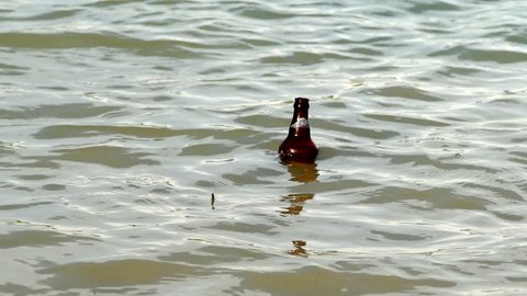a glass bottle drifting with waves,