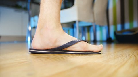 Flat feet in flip-flops walking in slow motion 4K. Low angle view of person's foot wearing flip-flops in focus while walking into frame and out. Home dining room in the background out of focus.