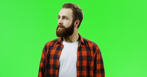 Portrait of the handsome caucasian man with a beard and in the red plaid shirt turning to the camera and crossing his hands while smiling. Green screen. Chroma key.