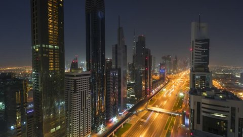 Day to night time lapse of modern downtown of Dubai. Burj Khalifa on background. Moving blur cars on Sheikh Zayed road.