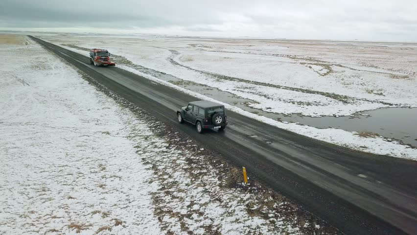 HOFN, ICELAND - MAY 04, 2018. Jeep Wrangler Unlimited driving in Icelandic countryside, aerial drone footage. Gravel roads ar common in Iceland. Accelerating with smoke from exhaust on throttle