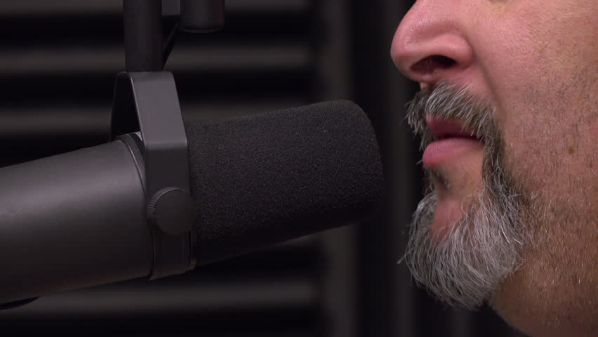 Middle aged man being interviewed on radio show talking into microphone.  | Shutterstock HD Video #1011693599