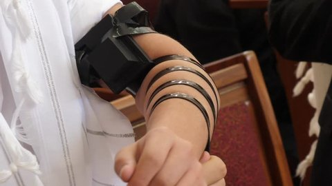 The laying of Tefillin Jewish man put on the hand a tefillin