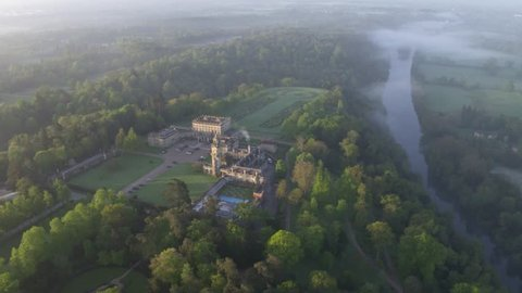 Aerial view / Drone Shot of Cliveden House in a wide frame, early morning, first light, whole estate with gardens, woodland and river within the shot and morning dew / fog in the shot, very English.