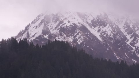Anchorage, Alaska circa-2018. Aerial view of snowy mountains and trees in fog near Anchorage, Alaska. Shot from helicopter with Cineflex gimbal and RED Epic-W camera.