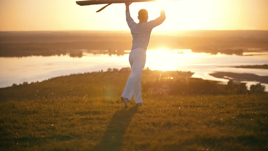 Male silhouette throws a wooden log on the grass at summer sunset on the hill | Shutterstock HD Video #1011729899